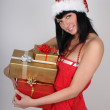 Happy brunette woman in santa hat holding golden and red present — Stock Photo