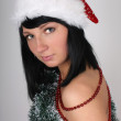 Beautiful brunette woman in santa hat with christmas tree decora — Stock Photo