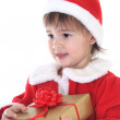 Little girl in santa clothes with gift — Stock Photo