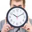 Stock Photo: Young businessman holding a clock