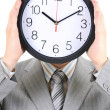 Man in gray suit holding big clock covering his face — Stock Photo