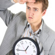 Tired businessman in grey suit holding a clock — Stock Photo #11791374