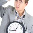 Amazed businessman in grey suit holding a clock — Stock Photo #11791377