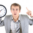 Amazed businessman in grey suit holding a clock — Stock Photo