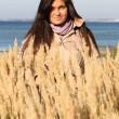 Woman in autumn coat standing at beach — Stock Photo
