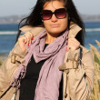Woman in beige autumn coat standing at beach — Stock Photo