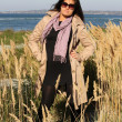 Woman in beige autumn coat standing at seaside — Stock Photo