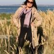 Woman in beige autumn coat standing at seaside — Stock Photo