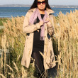 Woman in beige autumn coat standing by the sea — Stock Photo #11792766