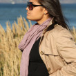 Stock Photo: Woman in beige autumn coat standing by the sea