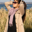 Attractive girl in beige autumn coat correcting her hair — Stock Photo #11792775