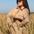 Stock Photo: Woman in beige autumn coat and sunglasses posing