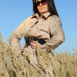 Stock Photo: Beautiful woman in beige autumn coat and sunglasses posing