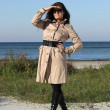 Woman in beige autumn coat and sunglasses posing by the sea — Stock Photo