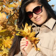 Beautiful womin beige autumn coat with golden leafage — Stok Fotoğraf #11792800
