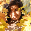 Foto Stock: Beautiful womwith golden leafage