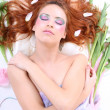 Red-haired woman with petals lying — Stock Photo