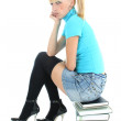 Sad schoolgirl sitting on stacked books — Stock Photo