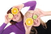 Två funny kvinnor med orange och lime skivor i stället för ögon — Stockfoto