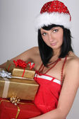 Beautiful brunette woman in santa hat holding golden and red pre — Stockfoto
