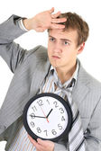 Tired businessman in grey suit holding a clock — Stock Photo