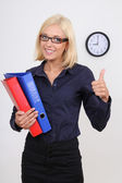 Businesswoman with folders thumbs up — Stock Photo