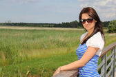 Beautiful woman standing in the field in summer time — Stock Photo
