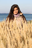 Frau im herbst mantel stehen am strand — Stockfoto