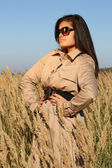 Woman in beige autumn coat and sunglasses posing — Stock Photo