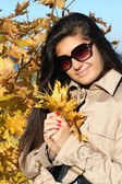 Beautiful woman in beige autumn coat with golden leafage — Stock Photo