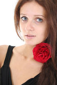 Portrait of girl with red rose in her hair — Stock Photo