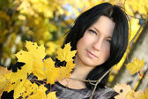 Attractive woman with yellow leafage — Stock Photo