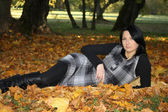 Attractive woman lying on yellow leafage — Stock Photo