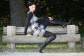 Attractive woman posing on bench in the autumn park — Stock Photo