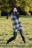 Girl in checkered dress posing in autumn park — Stock Photo