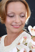 Portrait of attractive woman with orchid — Stock Photo