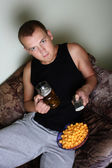 Man watching tv with beer and chips — Stock Photo
