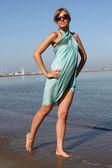 Mujer con vestido y gafas de sol en la playa — Foto de Stock