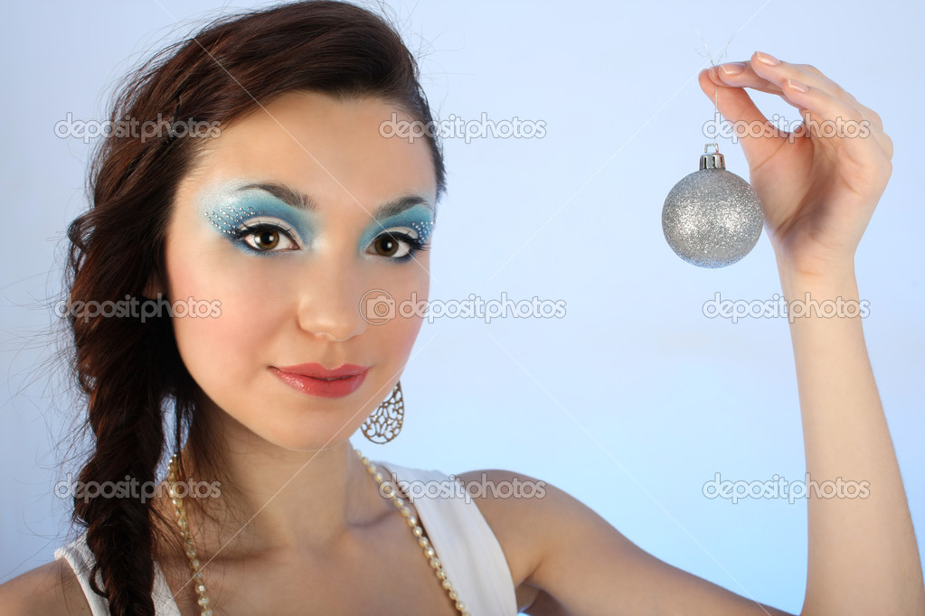 Beautiful woman with christmas tree ball over blue background — Stock fotografie #11791131