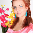 Red-haired woman with yellow and pink orchid — Stock Photo