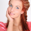 Beautiful red-haired woman in pink smiling — Stock Photo