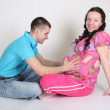 Man and pregnant woman sitting - Stock Photo