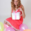 Sitting in balloons birthday girl with gift — Stock Photo
