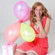 Birthday girl with gift and balloons showing shh sign — Stock Photo #11839868