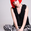 Young woman in red wig sitting — Stock Photo #11839911