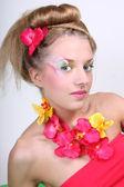 Schöne frau mit blumen und kreativen make-up — Stockfoto