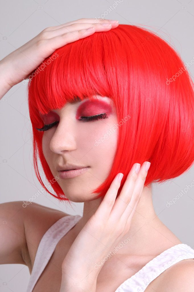 Attractive woman in red wig over grey — Stock Photo #11839107