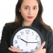 Businesswoman in suit holding a clock — Stock Photo #11840148