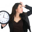 Shocked businesswoman with clock — Stockfoto