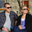 Smiling couple in sunglasses sitting on the bench — Stock Photo